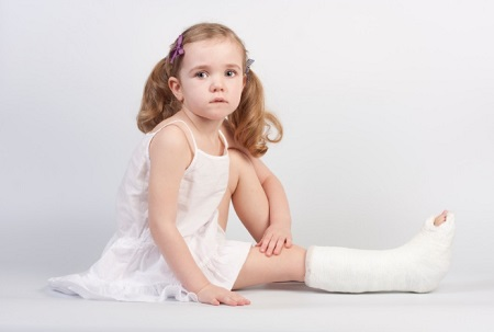 Little girl injured with broken ankle sitting on white backgound.